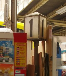 自販機の間に古い番線案内が挟まっている様子