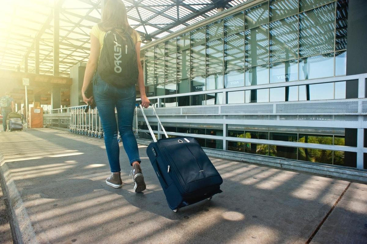 英語で旅行する女の子とトランク飛行場風景
