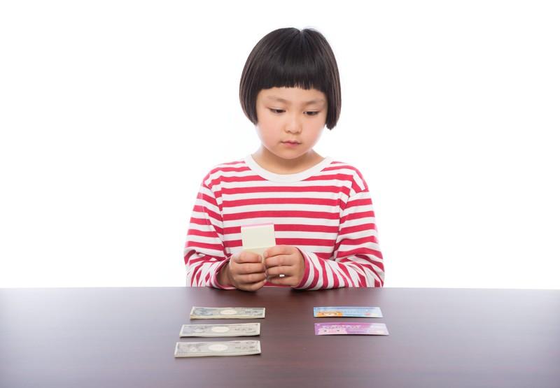 幼稚園の支払いに必要なお金を眺める子ども