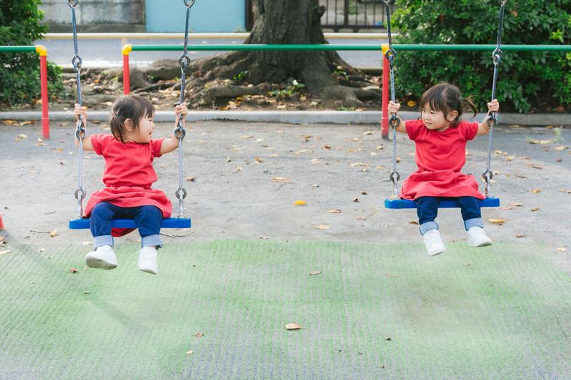 幼稚園のブランコで遊ぶ子ども達