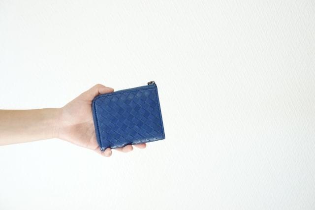 手で青い二つ折り財布を持っている