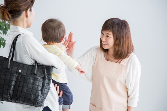お母さんに抱っこされた子どもが保育士さんとハイタッチしている