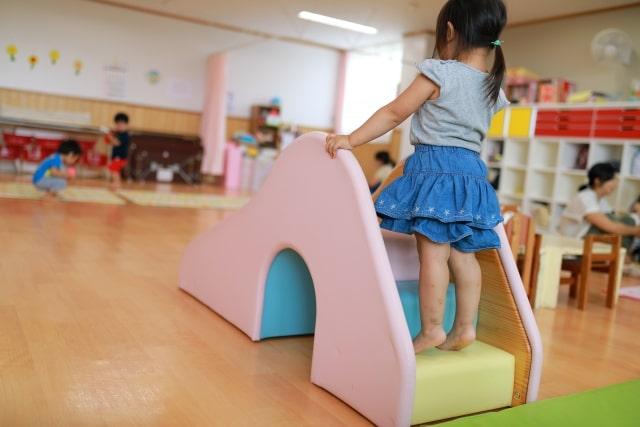 室内で女の子が滑り台で遊んでいる