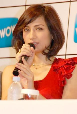赤いオフショルダーのドレスを着てマイクを握っている佐田真由美の画像