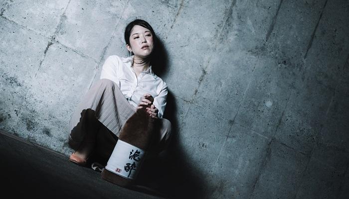 一人ぼっちで一升瓶を抱える女性