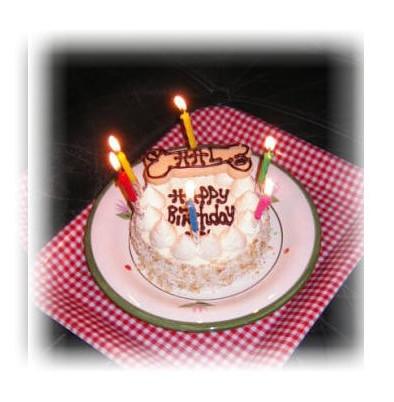 火の付いたロウソク6本が立ったワンコの誕生日ケーキ