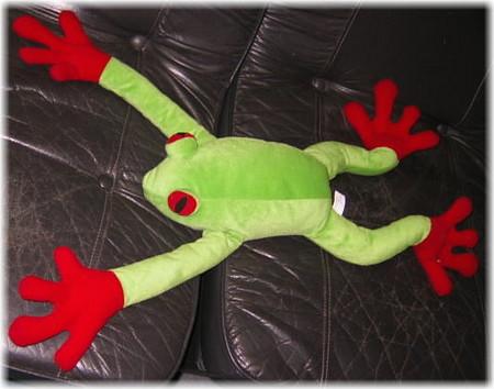 同体は緑色、手足は赤色のでっかくて手足が長いカエルの縫いぐるみの写真