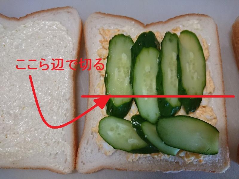 キュウリと卵のサンドイッチ切る位置を指す