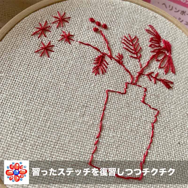 赤い手縫い糸で花瓶と花を刺繍中