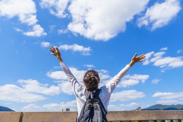 青空に向かってバンザイをする女性