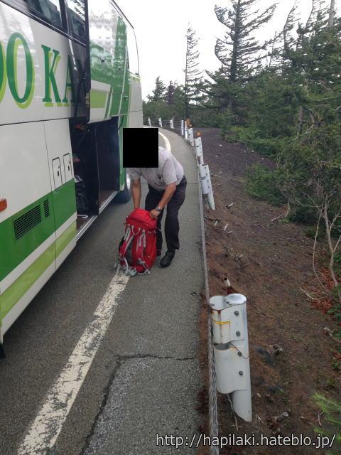 バスの荷物を下ろすドライバー