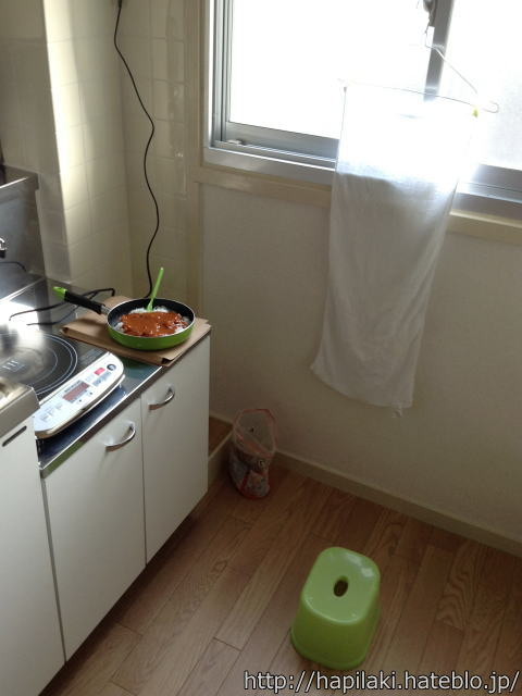 テーブル代わりのガスコンロ台でレトルトカレーを風呂椅子に座って食べる