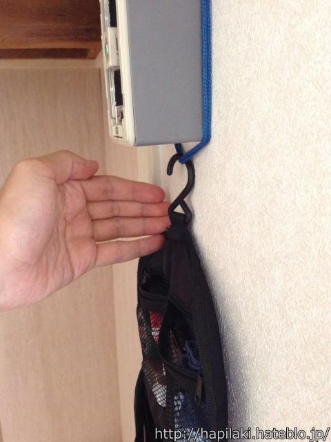 テレビのアンテナ端子に紐を掛けてトラベルポーチを吊るす