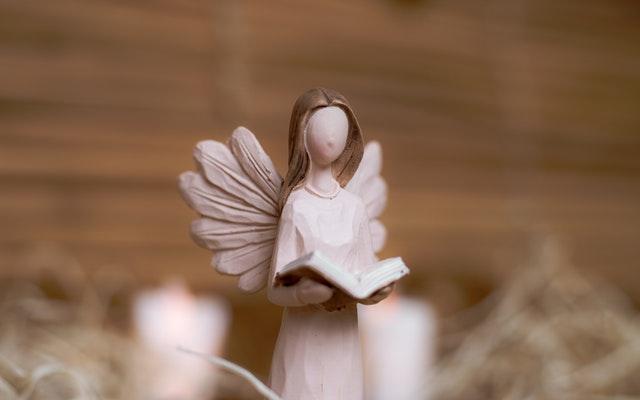 天使の人形が聖書を読んでいる