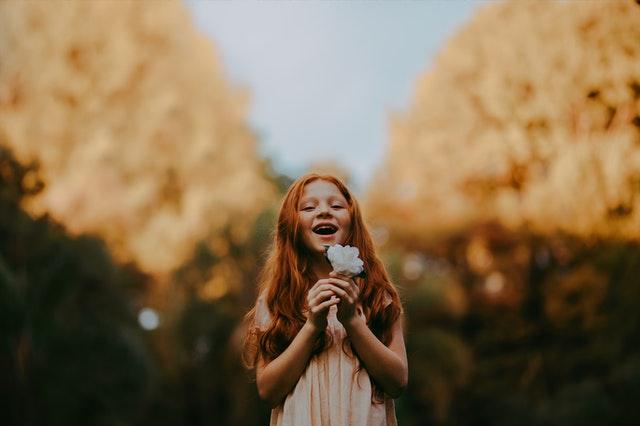小さな女の子が花を持って笑っている