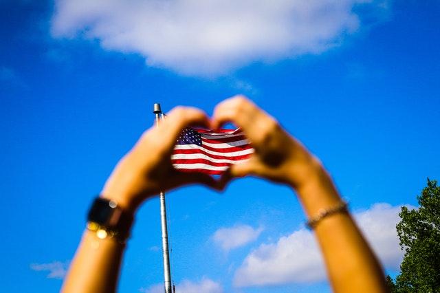 アメリカ国旗のハートを手で作っている
