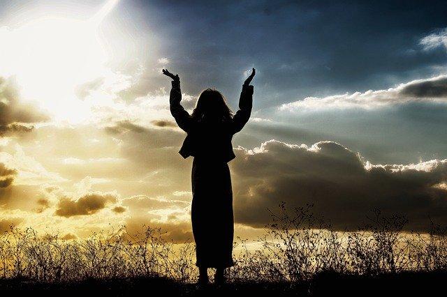 空に向かって祈りを捧げる女性