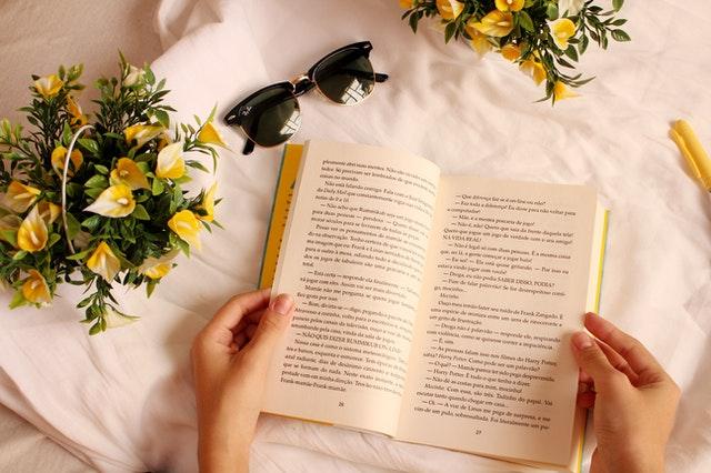 花に囲まれながら聖書を読んでいる