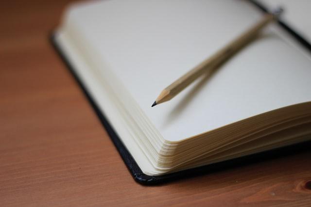 デスノートのようなノートの上に鉛筆がある