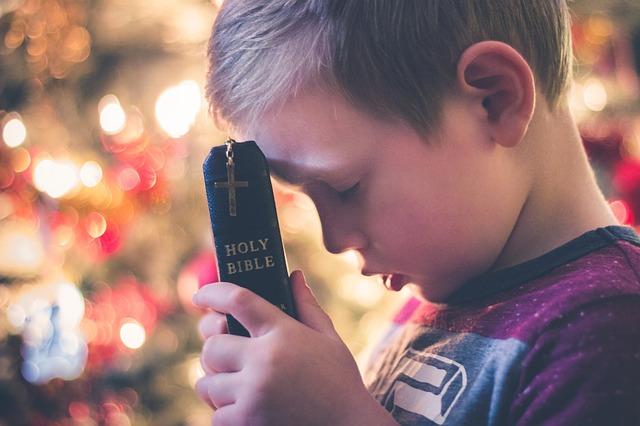聖書を握りしめてオデコにあてている男の子