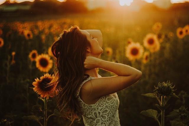 無数のひまわりに囲まれて、夕日に照らされる西洋の女性