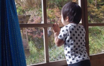窓の外を眺める男の子