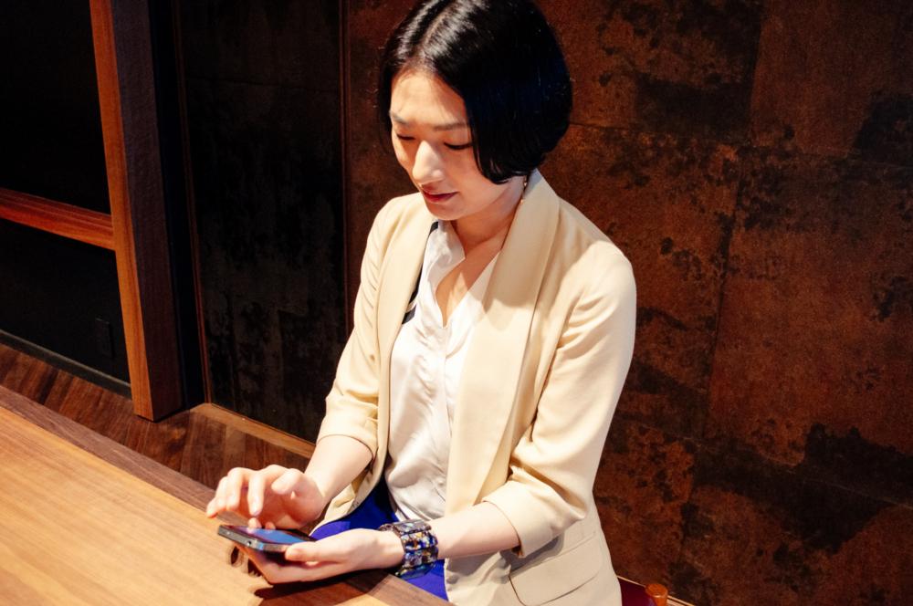 「B!KUMA ガールズ」のiPhoneアプリを触る雨宮さん