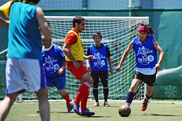 サッカーをするホームレスの男性