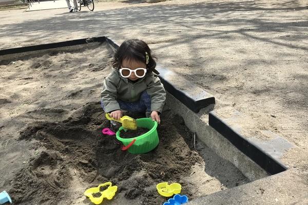 公園で砂遊びをする娘