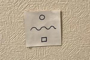 丸と四角と波線を7cm角の白い紙に中太のサインペンで記入し、坐の壁の高さ1/3の下部分に張り付ける子授けジンクス