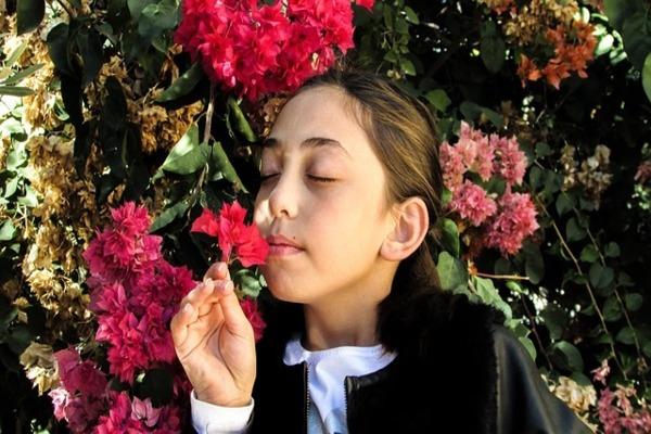 二人目妊活時に嗅覚を上げて妊娠しやすくするには、複数のアロマを交互に嗅いで、匂いの違いがわかるようになると良い。花の香りを嗅ぐ女の子。