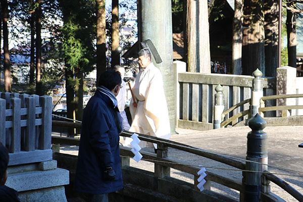 御手洗川に祈る神職