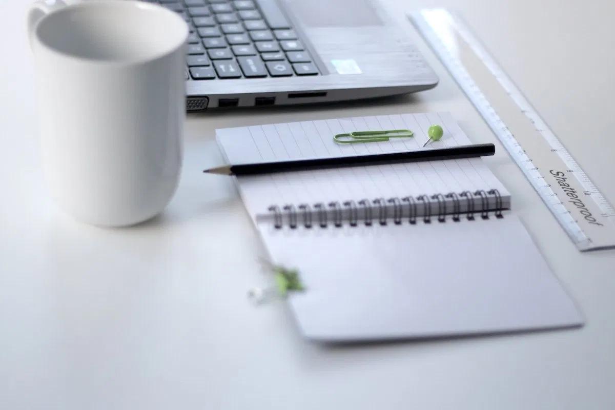 白いマグカップとノートとパソコン