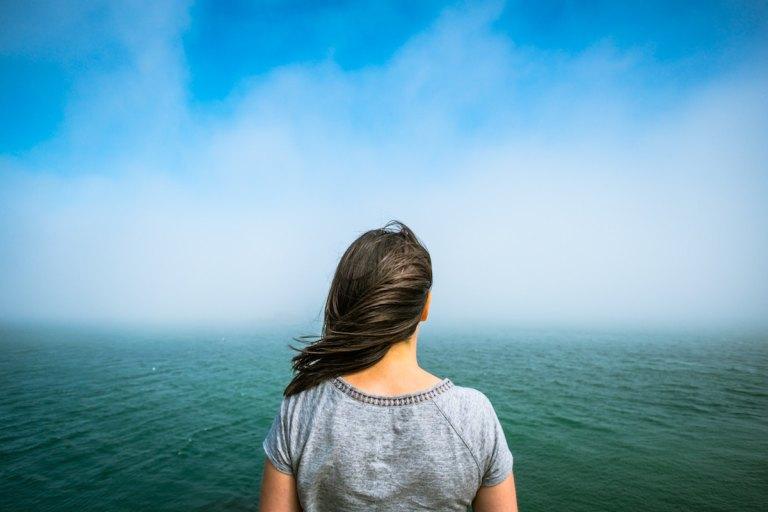 海に向かって立つ女性