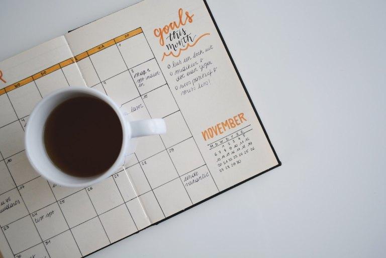 スケジュール帳の上に置かれたコーヒーカップ