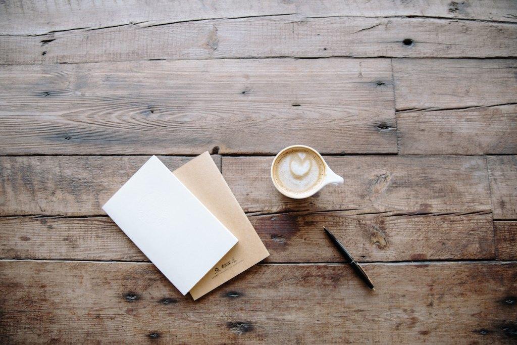 机の上の紙とカップとペン