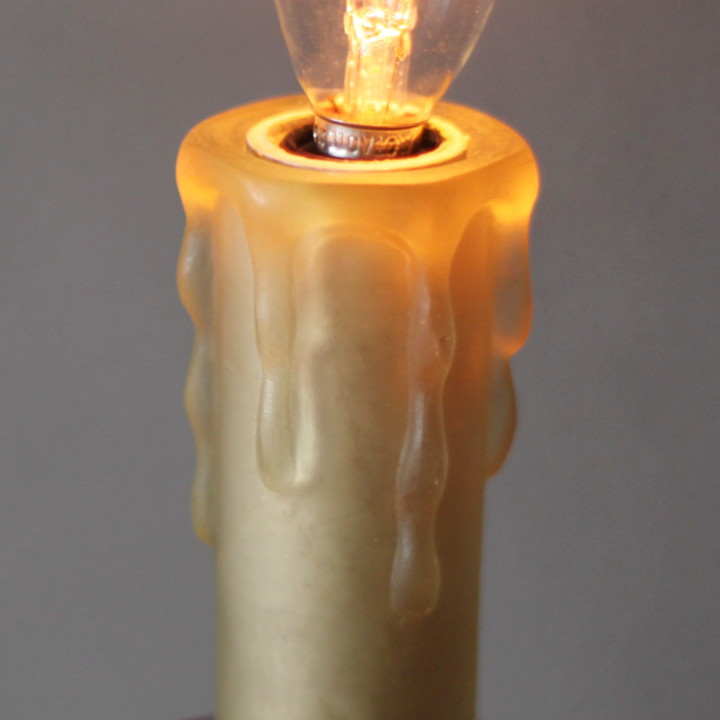 電球の光を受けて柔らかな光で包まれるプラスティック製のキャンドルカバー