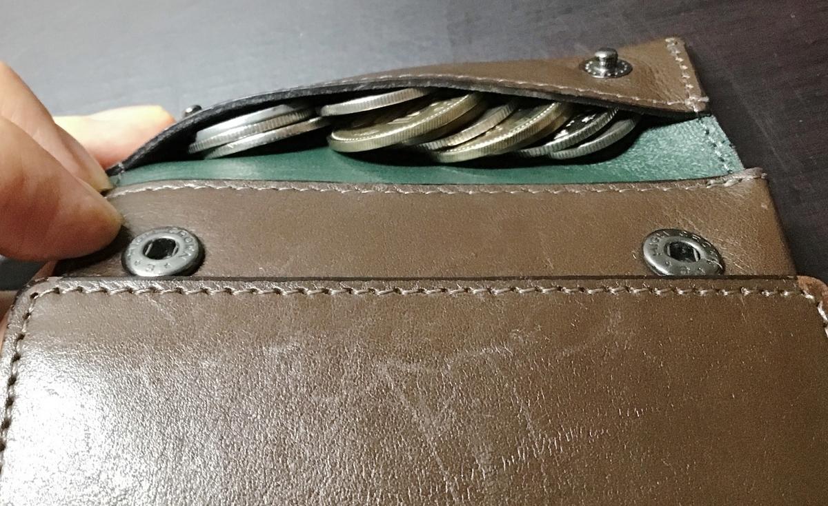 薄い財布に小銭を詰め込む