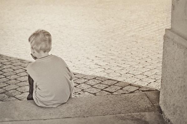 寂しそうに座っている少年の後ろ姿
