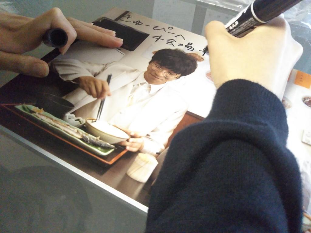 写真パネルにサインをしている様子