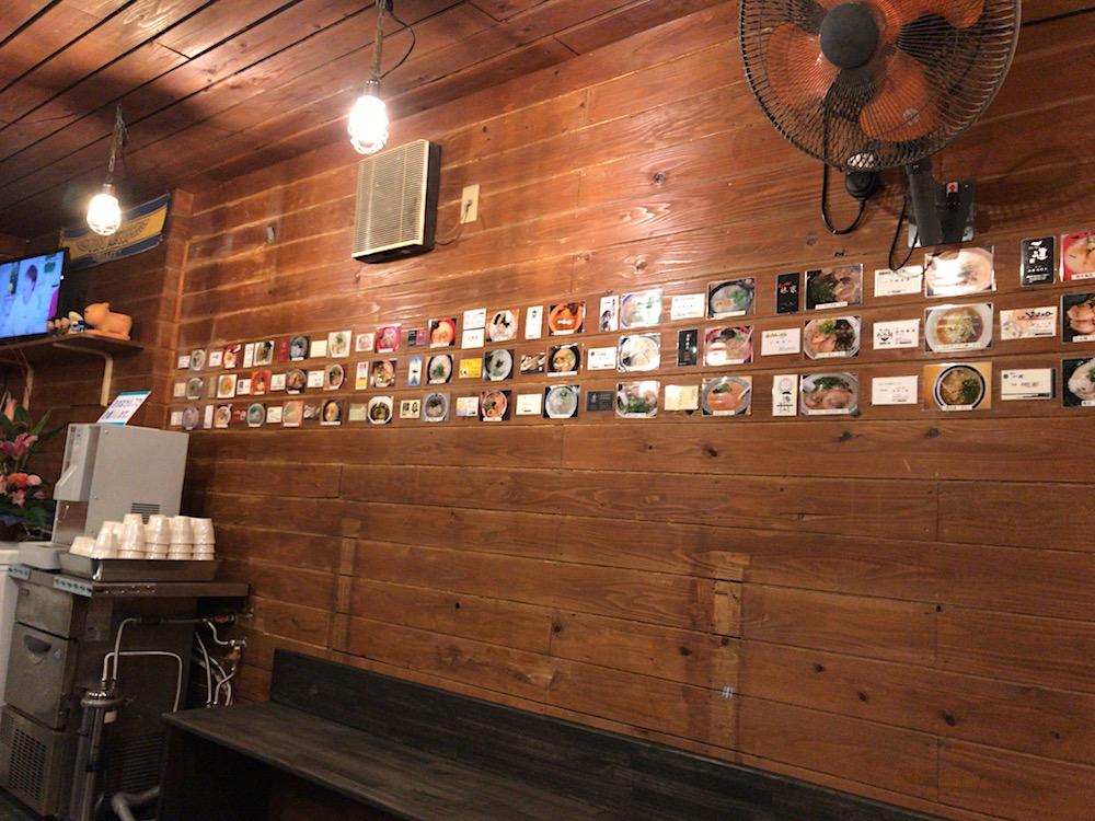 麺屋ぶらっくぴっぐ 壁のラーメン店の写真と名刺