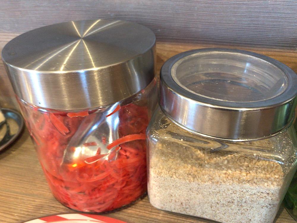 らーめん家MARU 机上の紅生姜とゴマには蓋つき容器