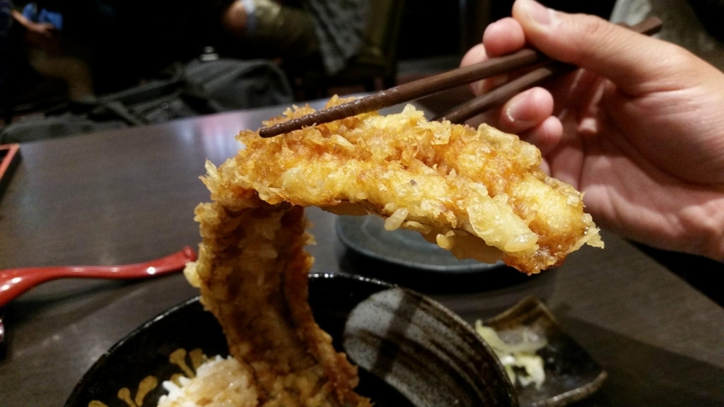 浅草『天丼秋光』の五代目天丼に乗っている、穴子の天ぷらを箸で持ち上げた写真