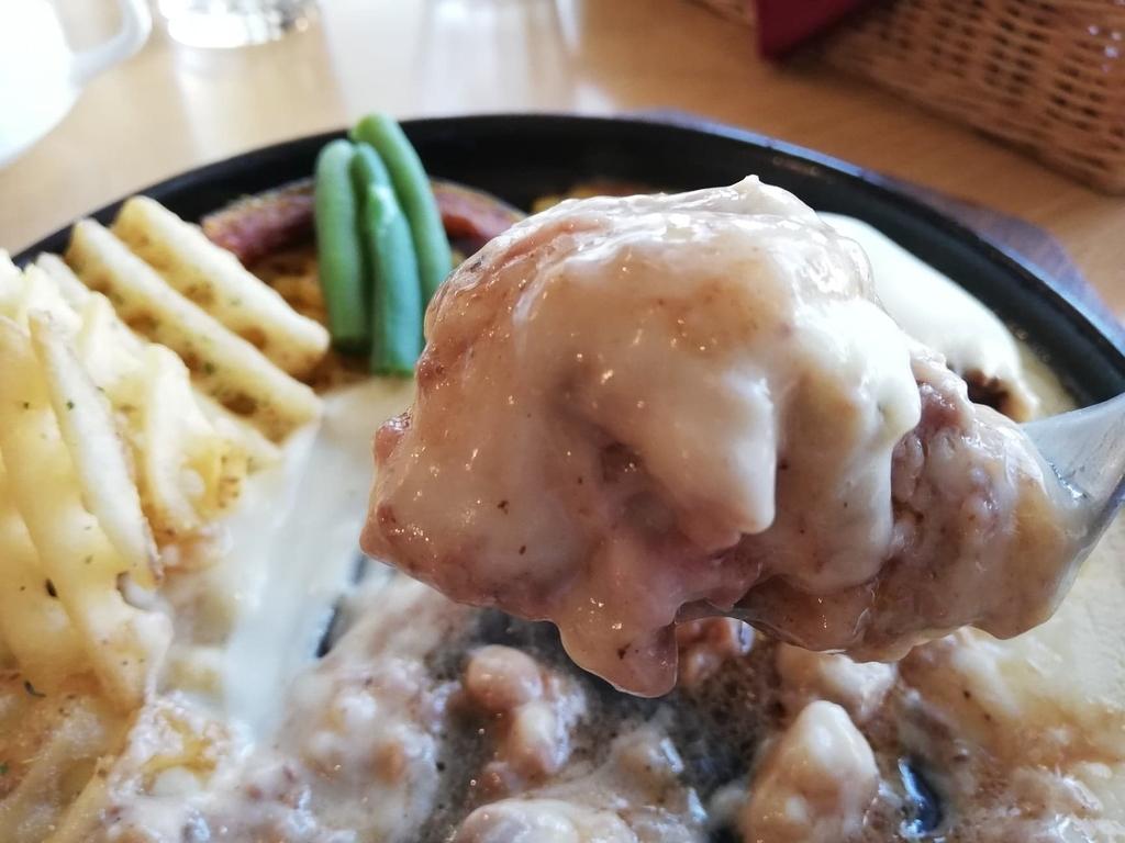 フォークですくったホワイトチーズハンバーグと油のカタマリ
