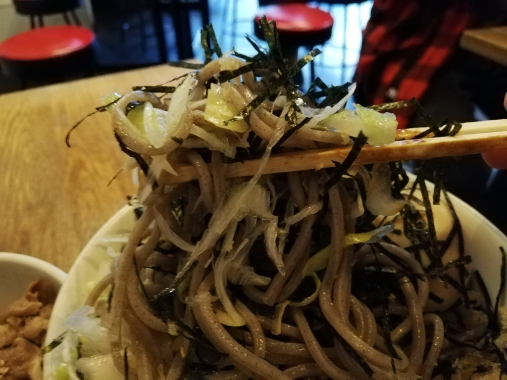 箸で持ち上げた麺とネギと海苔のアップ