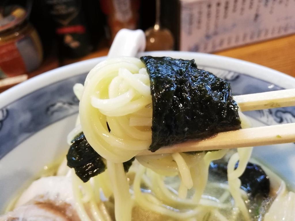 箸で掴んだ特選塩ラーメンの麺と海苔