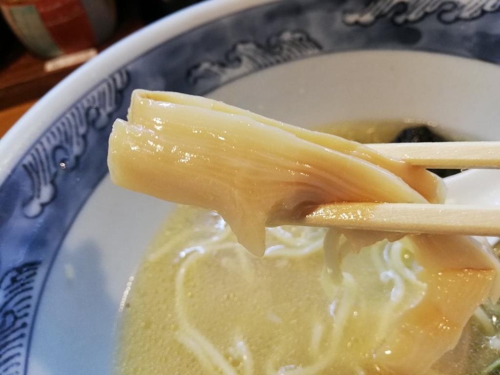 箸で掴んだ特選塩ラーメンのメンマ