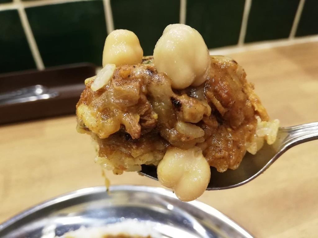 スプーンですくった高田馬場『プネウマカレー』のチキンカレーとひよこ豆のピクルス
