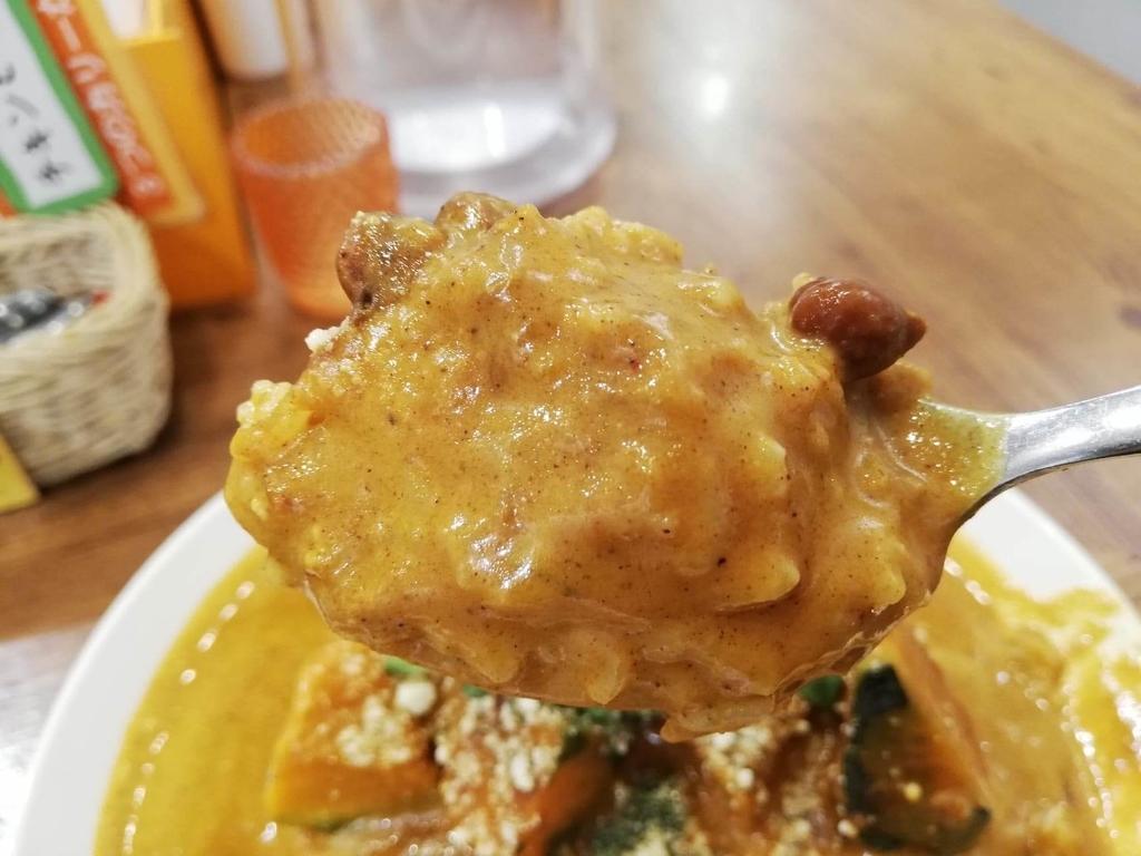 スプーンですくったヤミツキカリー西池袋店のホクホクかぼちゃのチーズカリー特盛の豆とカレーライス