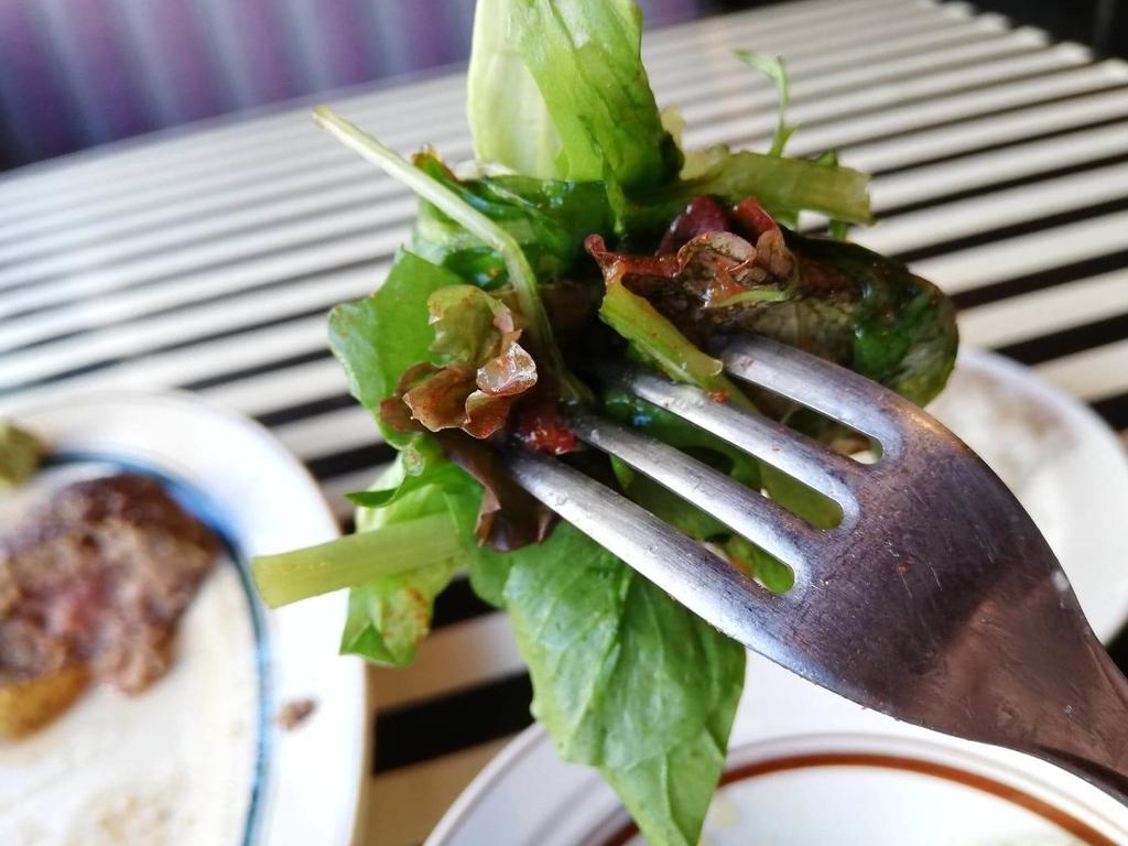 フォークで刺した、池袋『Gottie's BEEF(ゴッチーズビーフ)』のプレミアムハンバーグ&極太ソーセージの付け合わせのサラダ
